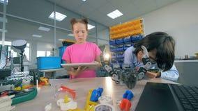 Jonge geitjes die een stuk speelgoed robot construeren Twee kinderen construeren een robot in een laboratoriumruimte stock videobeelden