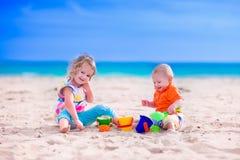 Jonge geitjes die een zandkasteel bouwen op een strand Stock Foto's