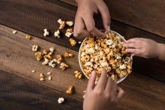 3 jonge geitjes die etend popcorn in een kom delen stock afbeeldingen