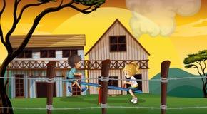 Jonge geitjes die geschommel voor houten barnhouses spelen Stock Fotografie