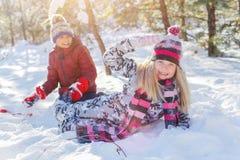 Jonge geitjes die in grote sneeuw in de winter spelen stock afbeelding