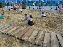 Jonge geitjes die in grote zandbak, het Park van Sotchi, Rusland spelen Stock Afbeelding