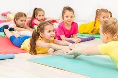 Jonge geitjes die gymnastiek met vrouwelijke leraar uitoefenen Royalty-vrije Stock Foto