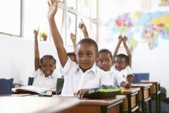 Jonge geitjes die handen opheffen tijdens een les op een basisschool Stock Foto