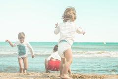 Jonge geitjes die in het zand op het strand spelen Jonge kinderen die op het strand spelen Stock Afbeeldingen