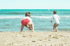 Jonge geitjes die in het zand op het strand spelen Jonge kinderen die op het strand spelen Stock Foto