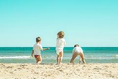 Jonge geitjes die in het zand op het strand spelen Jonge kinderen die op het strand spelen Stock Afbeelding