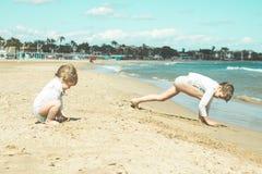 Jonge geitjes die in het zand op het strand spelen Jonge kinderen die op het strand spelen Royalty-vrije Stock Afbeelding