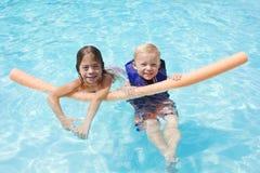 Jonge geitjes die in het zwembad samen spelen Stock Afbeelding