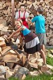 Jonge geitjes die hun vader helpen om het gehakte brandhout te stapelen stock afbeeldingen