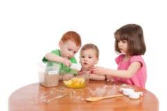 Jonge geitjes die ingrediënten voor baksel in keuken meten Royalty-vrije Stock Afbeeldingen
