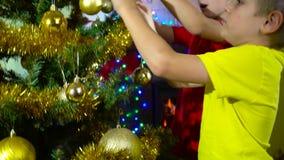 Jonge geitjes die Kerstboom verfraaien stock footage