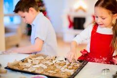 Jonge geitjes die Kerstmiskoekjes bakken Stock Afbeeldingen