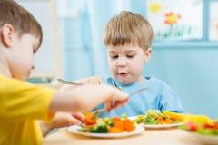 Jonge geitjes die in kleuterschool eten Stock Afbeelding