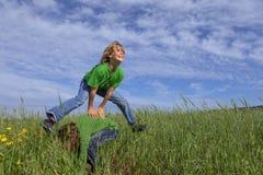 Jonge geitjes die leapfrog de zomerspel spelen royalty-vrije stock fotografie