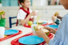Jonge geitjes die lunch eten op school stock afbeeldingen