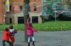Jonge geitjes die met de zeepbels in Londen spelen Stock Afbeelding