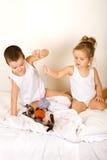 Jonge geitjes die met hun katje op het bed spelen stock fotografie