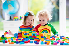 Jonge geitjes die met kleurrijke plastic blokken spelen Stock Afbeeldingen
