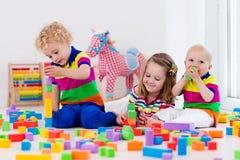 Jonge geitjes die met kleurrijke stuk speelgoed blokken spelen Stock Foto