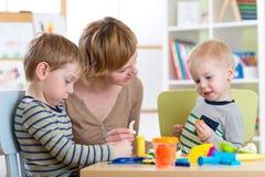 Jonge geitjes die met spelklei thuis of kleuterschool of playschool spelen stock afbeeldingen