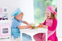 Jonge geitjes die met stuk speelgoed keuken spelen Stock Fotografie