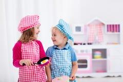 Jonge geitjes die met stuk speelgoed keuken spelen Stock Afbeelding