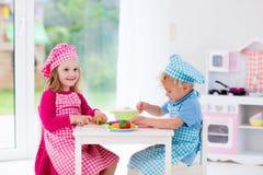 Jonge geitjes die met stuk speelgoed keuken spelen Stock Foto's