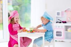 Jonge geitjes die met stuk speelgoed keuken spelen Stock Afbeeldingen