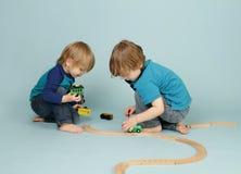 Jonge geitjes die met stuk speelgoed treinen spelen Stock Afbeeldingen