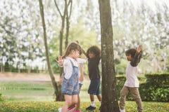 Jonge geitjes die met vrienden bij park spelen stock afbeelding