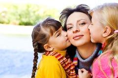Jonge geitjes die moeder kussen Stock Fotografie