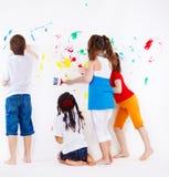 Jonge geitjes die muur schilderen Stock Foto's