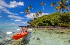Jonge geitjes die in oceaan kayaking Stock Afbeeldingen