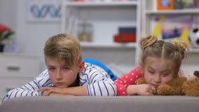 Jonge geitjes die op bank liggen en camerajongen de bekijken vermoeiden na baby-sitting met zuster stock videobeelden