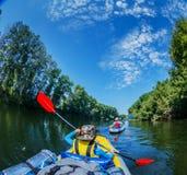 Jonge geitjes die op de rivier op een zonnige dag tijdens de zomervakantie kayaking stock foto