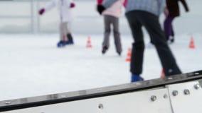 Jonge geitjes die op ijs voorbij de hindernissen op ijsbaan schaatsen stock footage