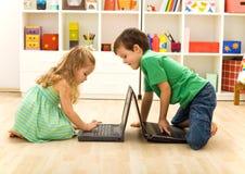 Jonge geitjes die op laptops spelen Stock Foto's