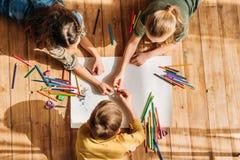 Jonge geitjes die op papier met potloden trekken terwijl het liggen op vloer Stock Afbeeldingen
