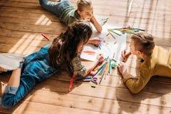 Jonge geitjes die op papier met potloden trekken terwijl het liggen op vloer Royalty-vrije Stock Afbeeldingen