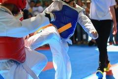 Jonge geitjes die op stadium tijdens Taekwondowedstrijd vechten Stock Foto's