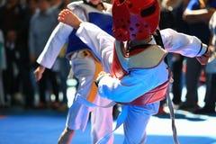Jonge geitjes die op stadium tijdens Taekwondowedstrijd vechten Stock Foto