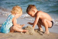 Jonge geitjes die op strand spelen Royalty-vrije Stock Afbeelding