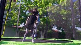 Jonge geitjes die op trampoline, langzame motie springen - 02 stock videobeelden