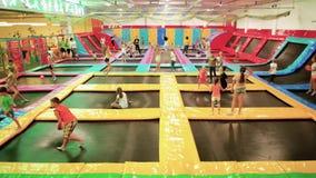 Jonge geitjes die op trampolines, kinderen springen die pret samen in lokaal pretpark, sportactiviteiten hebben stock footage