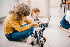 jonge geitjes die op vloer bij machinesklasse zitten, stam royalty-vrije stock afbeeldingen