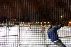 Jonge geitjes die openluchthockey op ijs spelen bij nacht in een park van Quebec, Canada - 2/3 stock foto