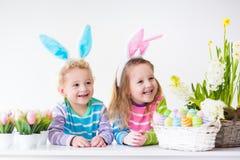Jonge geitjes die Pasen thuis vieren Stock Afbeeldingen