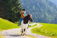 Jonge geitjes die poney berijden Kind op paard in de bergen van Alpen stock afbeelding