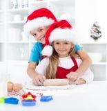 Jonge geitjes die pret hebben die Kerstmiskoekjes voorbereidt Stock Foto's
